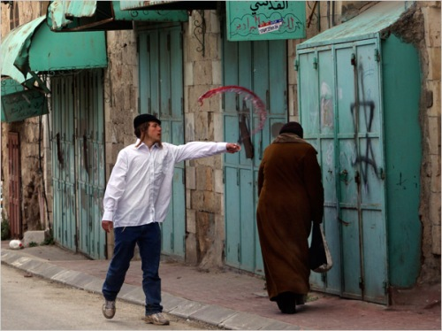 Zionist throwing wine at passing Palestinian Woman